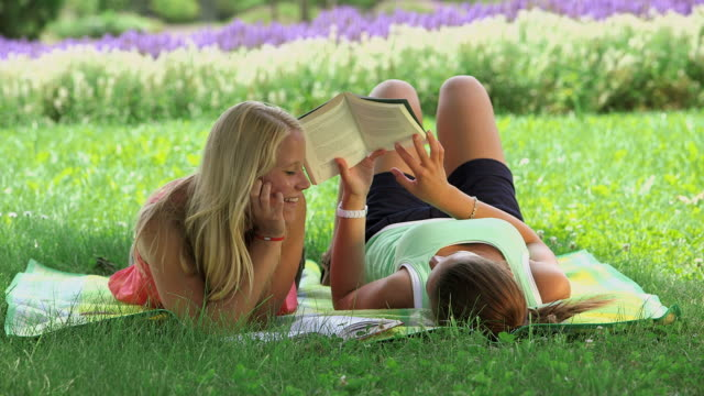 vídeos de stock e filmes b-roll de ms shot of girls laying in park on blanket reading book and talking with each other/ losheim am see, saarland, germany - só meninas adolescentes