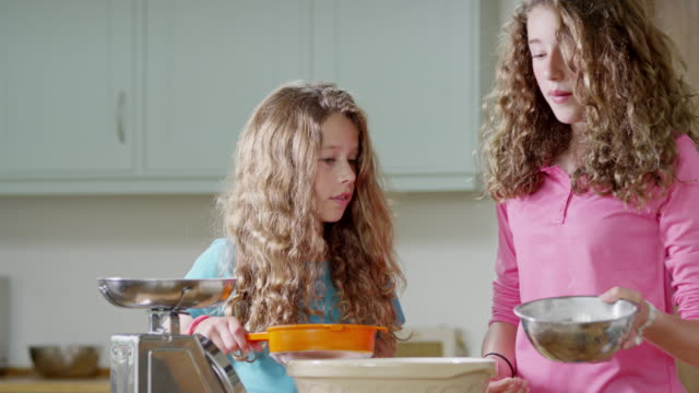 ms slo mo shot of girls pouring flour in to mixing bowl / london, hampstead, united kingdom - mixing bowl stock videos and b-roll footage