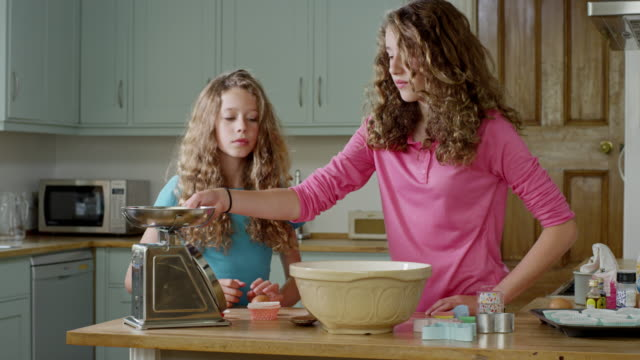 ms shot of girls preparing to bake while in kitchen, by pouring ingredients in to mixing bowl / london, hampstead, united kingdom - mixing bowl stock videos and b-roll footage
