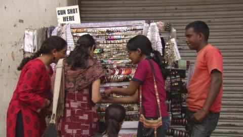 ms td tu shot of girls purchasing on stall at city street / bangalore, india - mellanstor grupp av människor bildbanksvideor och videomaterial från bakom kulisserna