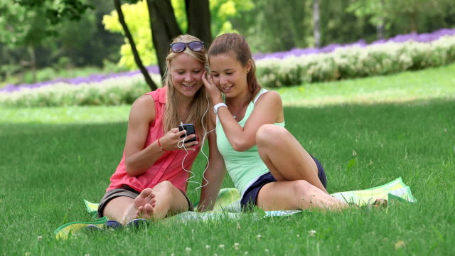 ms shot of girls sitting in park on blanket and listening to music on smartphone / losheim am see, saarland, germany - enjoyment点の映像素材/bロール