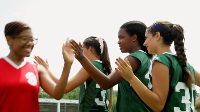 vídeos y material grabado en eventos de stock de ms shot of girls softball team do high five with other team / albany, new york, united states  - sófbol