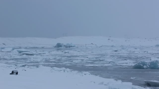 ms pan shot of glaciers detail at jokulsarlon lagoon with snow covers glaciers and lakeside / iceland - 1 minute or greater stock videos & royalty-free footage