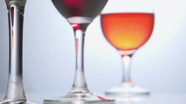 ecu r/f slo mo shot of glass of red and pink wine against white background / calvados, normandy, france - calvados stock videos and b-roll footage