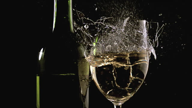 ms slo mo shot of glass of white wine breaking and splashing against black background / calvados, normandy, france - wine glass stock videos and b-roll footage