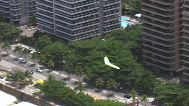 MS AERIAL ZI TS Shot of Glider flying over beach / Rio de Janeiro, Brazil