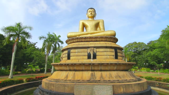 ms shot of golden seated buddha statue at viharamahadevi park (victoria park) / colombo, western province, sri lanka - sri lankan culture stock videos & royalty-free footage