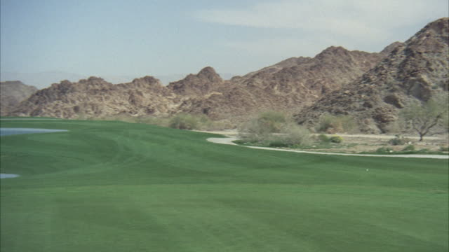 ms pan shot of golf course to golf cart on fairway - golf cart stock videos and b-roll footage