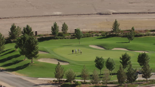vidéos et rushes de cu aerial zo shot of golfers swings and puts on turf at tuscany golf club and developing community / henderson, nevada, united states - nevada