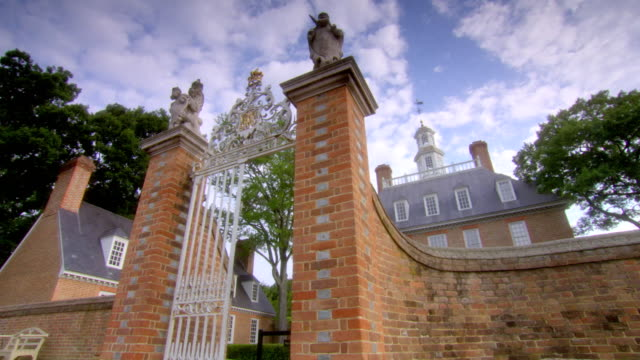 ms pan shot of governors palace building to ornate entrance gate in williamsburg / williamsburg, virginia, united states  - kolonialstil stock-videos und b-roll-filmmaterial