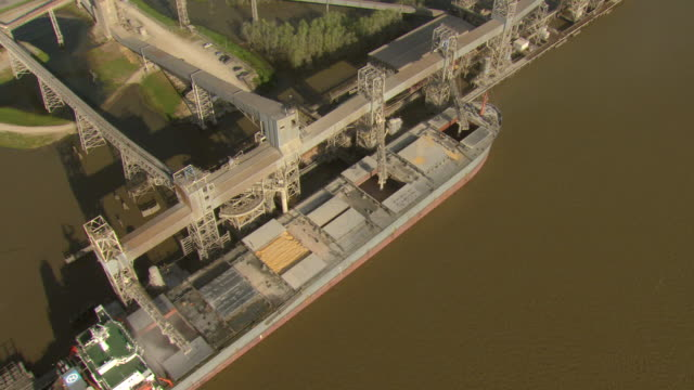 MS AERIAL Shot of grain loading on barge at port / New Orleans, Louisiana, United States
