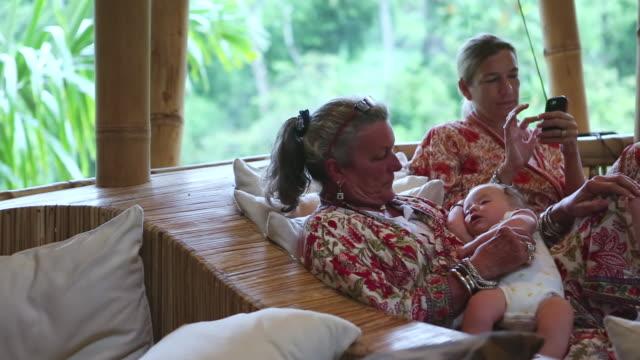 MS PAN Shot of grandmother holding sleeping baby while mom used her phone / Ubud, Bali, Indonesia