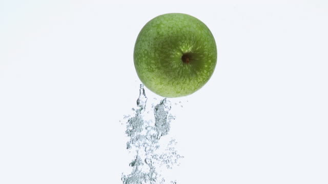 CU SLO MO Shot of Granny Smith Apple, malus domestica, Fruit entering Water against White Background / Calvados, Normandy, France