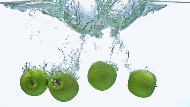 vídeos y material grabado en eventos de stock de cu td slo mo shot of granny smith apples, malus domestica, fruits entering water against white background / calvados, normandy, france - manzana