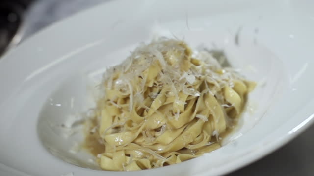 CU SLO MO Shot of Grated cheese falling into pasta dish / Sao Paulo, Brazil