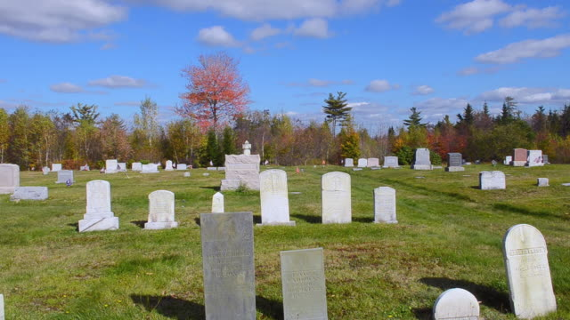 WS Shot of graveyard with tombstones with beautiful fall colors foliage in Northern New England in October / Ellsworth, Maine, United States