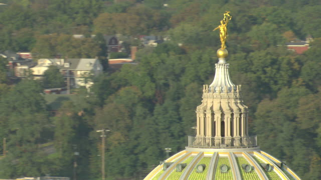 vídeos de stock e filmes b-roll de cu aerial shot of green dome and brass commonwealth statue at top of capitol building with downtown / harrisburg, pennsylvania, united states - edifício do capitólio