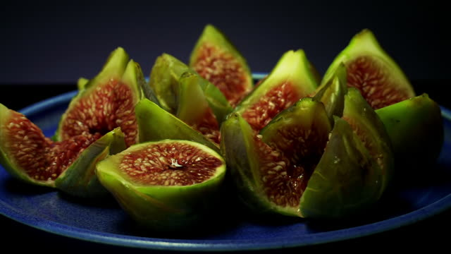 vídeos de stock, filmes e b-roll de ms shot of green figs rotate on blue plate / estepona,espana, malaga, spain   - enfoque de objeto sobre a mesa