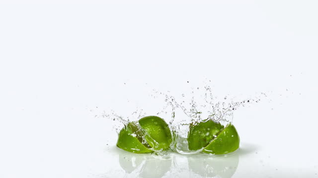 CU SLO MO Shot of Green Lemons, citrus aurantifolia, Fruits falling on Water and splashing against White Background / Calvados, Normandy, France