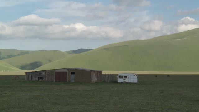ms shot of green valley meadow and mountain range / castelluccio di norcia, umbria, italie - pianura video stock e b–roll