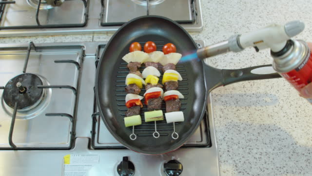 Shot of grilling skewers with torch