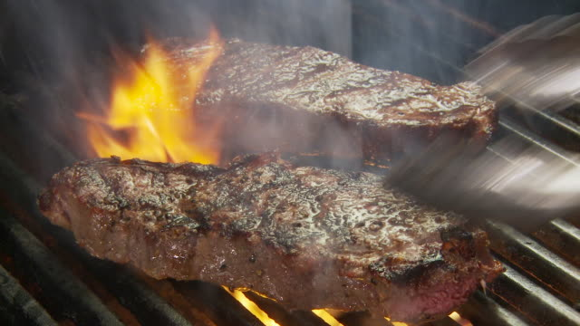 CU Shot of  grilling steaks with flame and smoke / Atlanta, GA, United States