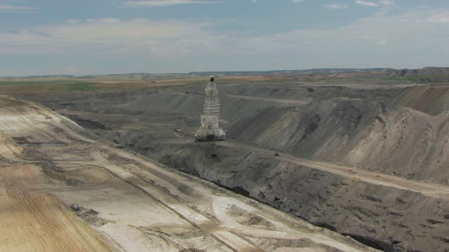 CU AERIAL TU TS Shot of Ground to reveal Ursa Major Dragline machine moving dirt in fresh coal trench / Wyoming, United States