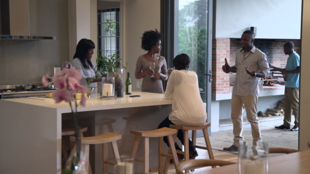 ws pan shot of group african friends preparing food and talking in kitchen / cape town, western cape, south africa - french food wine stock videos & royalty-free footage