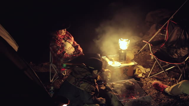 ms pan shot of group cooking food on bonfire at camping at night / okutama, tokyo, japan - キャンプする点の映像素材/bロール