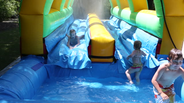 ws shot of group of children playing on an inflatable water slide / st simon's island, georgia, united states - water slide stock videos & royalty-free footage