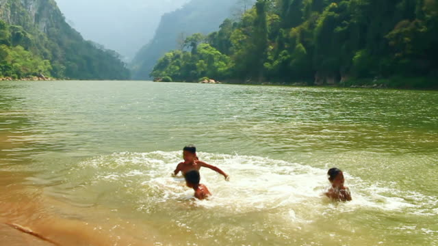 MS SLO MO Shot of group of children running and jumping all together into river / Muang Ngoi, Luang Prabang, Laos
