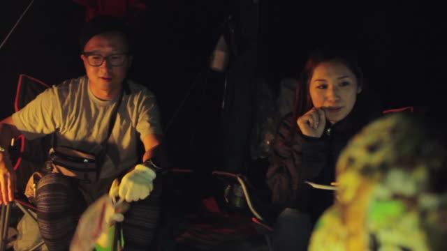 MS PAN Shot of group of friends chatting at camp site in night lamp / Okutama, Tokyo, Japan