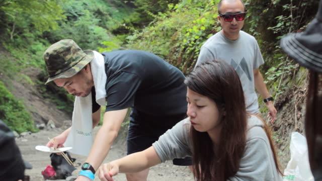 cu pan shot of group of friends cooking and eating at camping / okutama, tokyo, japan - キャンプする点の映像素材/bロール