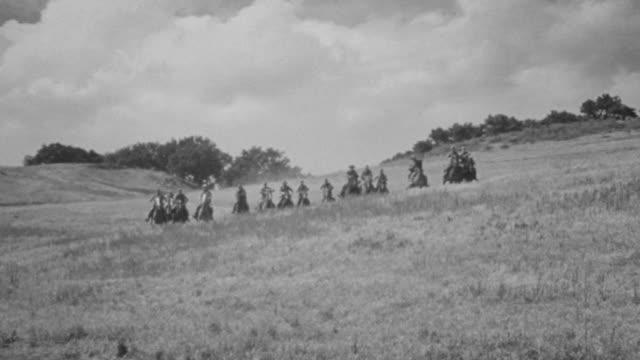 vídeos y material grabado en eventos de stock de ms shot of group of horseback riding fast moving through on empty field with some explosions in back side - galopar