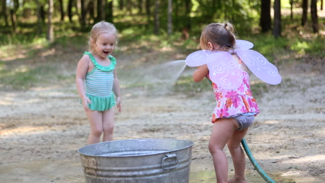 ws shot of group of little girls playing with hose / st simon's island, georgia, united states - hose stock videos & royalty-free footage
