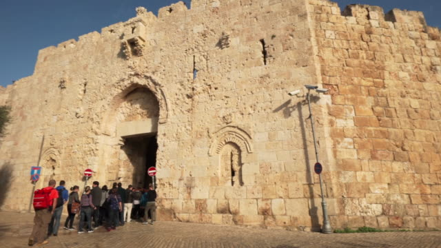 ws pan shot of  group of people enter zion gate of old city and stone wall and security cameras / jerusalem, israel - cancello video stock e b–roll