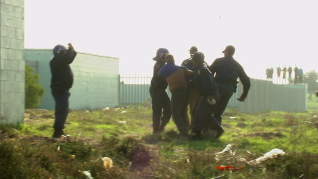 ws ts shot of group of policemen surrounding and pulling protester in mitchells plain township audio / cape town, south africa - authority stock-videos und b-roll-filmmaterial