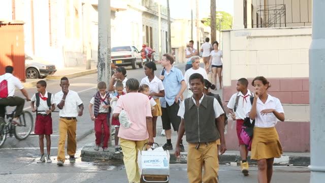 ms shot of group of school children crossing street at town / cuba - überqueren stock-videos und b-roll-filmmaterial