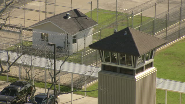MS AERIAL Shot of guard tower and barbed wire fence at louisiana state penitentiary / Angola, Louisiana, United States