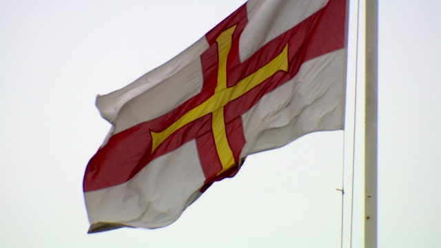 CU Shot of Guernsey Flag blowing / St. Peter Port, Guernsey, United Kingdom