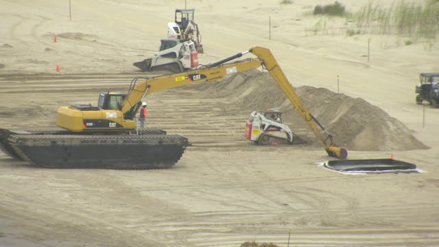 ms aerial shot of gulf coast bulldozers with clean up crews and trucks / louisiana, united states - bulldozer stock videos and b-roll footage