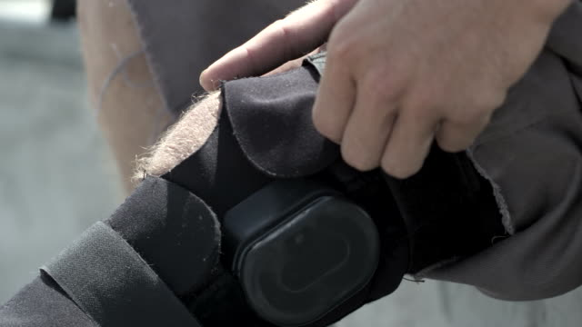 cu slo mo tu shot of guy adjusting leg brace / venice, california, united states - leg brace stock videos and b-roll footage