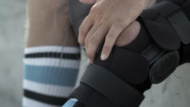 vídeos de stock, filmes e b-roll de cu slo mo tu shot of guy adjusting leg brace / venice, california, united states - brace