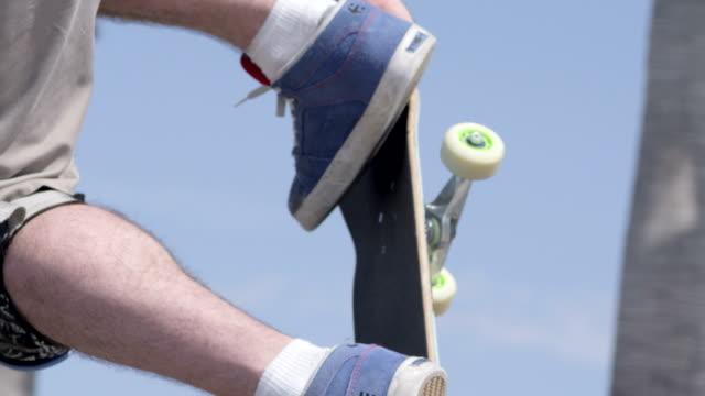 CU SLO MO TS Shot of guy doing aerial trick / Venice, California, United States