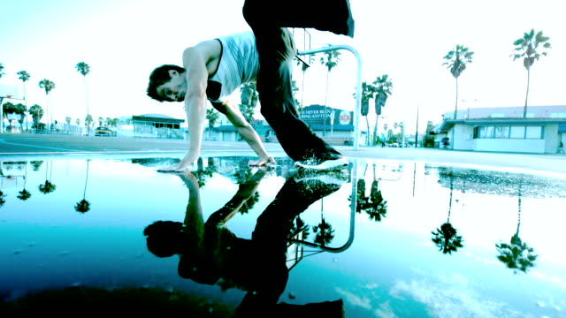 MS SLO MO LA Shot of Guy in white shirt flips and falls with reflection in water / Venice, California, United States