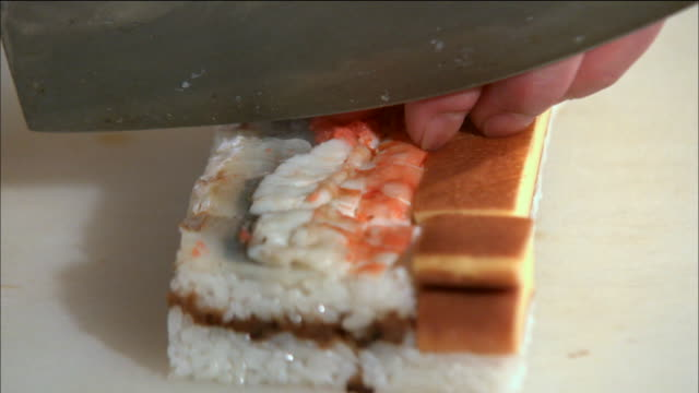 shot of hakozushi (box sushi) being cut with knife in osaka, japan - japanese food stock videos & royalty-free footage