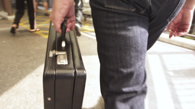 cu ts shot of hand carries black briefcase down travelator / hong kong, china - 書類鞄点の映像素材/bロール