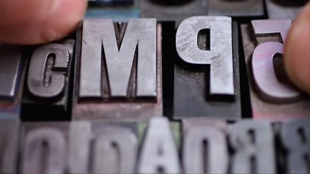ECU Shot of Hand collecting together number of letter press types / London, United Kingdom