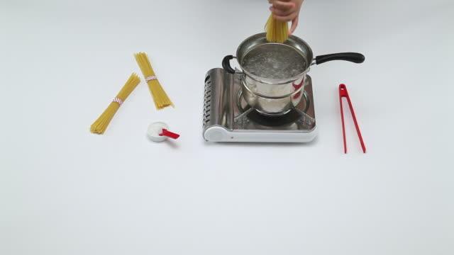 vídeos y material grabado en eventos de stock de ms shot of hand entering to dropping pasta noodles into boiler / seoul, south korea - hervido