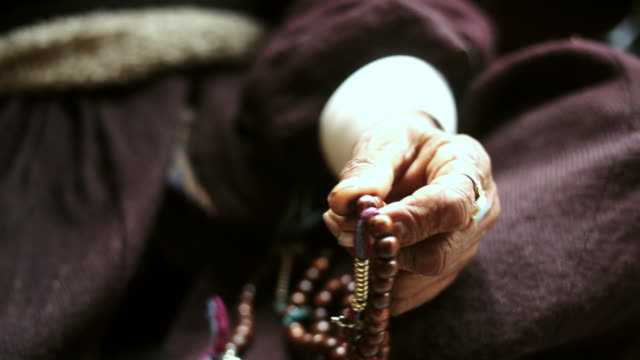 cu shot of hand of elderly woman using prayer beads in traditional way / ladakh, india  - prayer beads stock videos & royalty-free footage